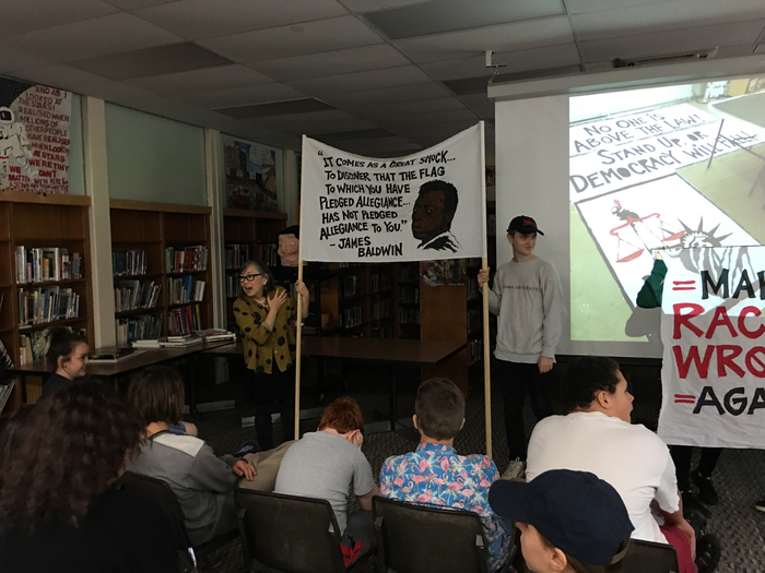 Artist Migiwa Orimo talking to 8th graders about her protest banners.